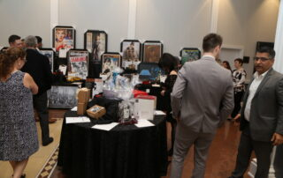 Various gift baskets and prizes showcase with people around them