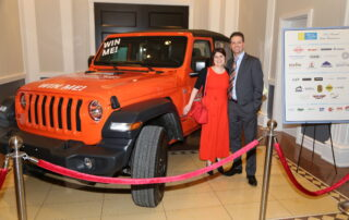 People posing with red Jeep Wrangler for raffle